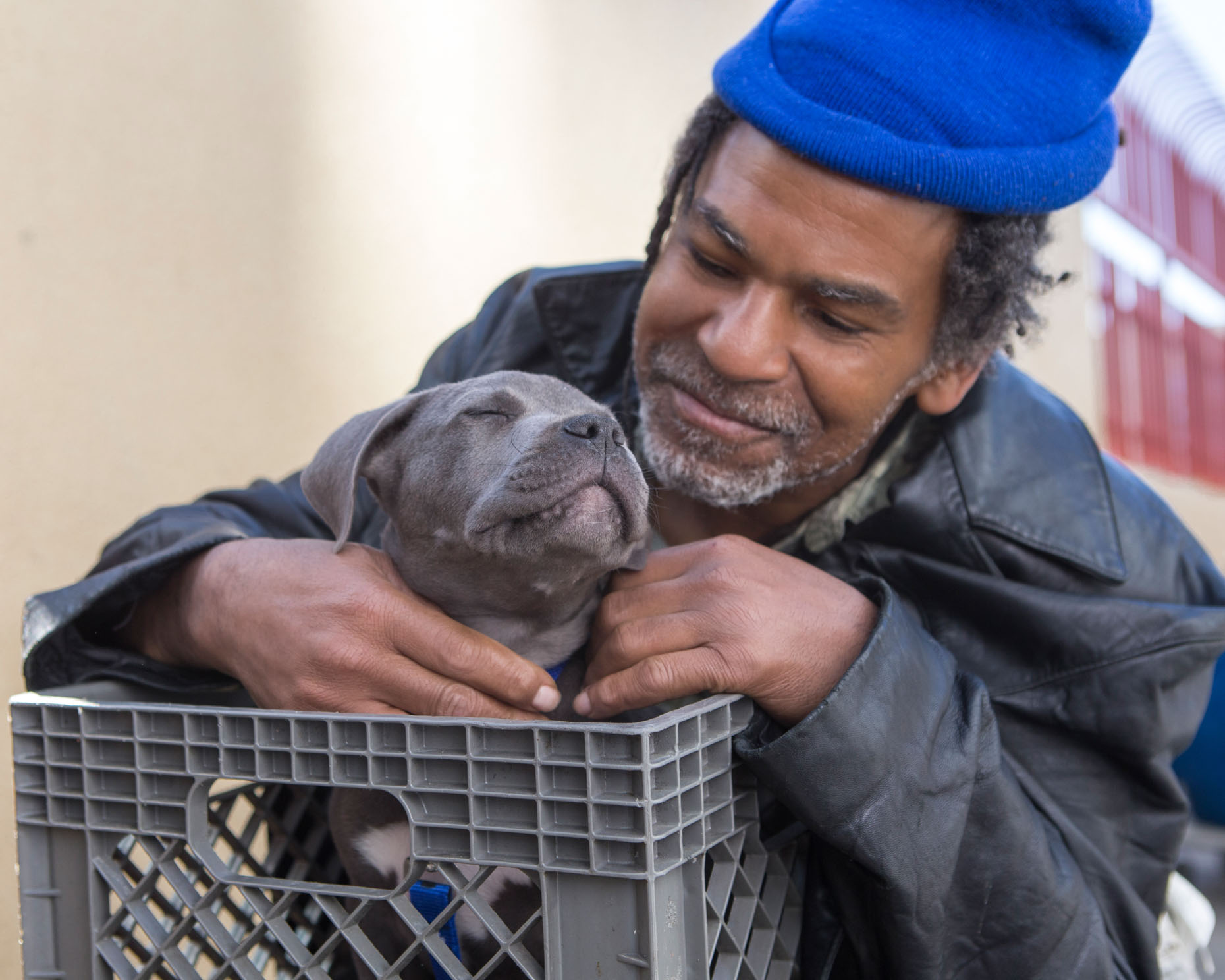 Editorial Photography | Man Holding Puppy in Milk Crate by Mark Rogers